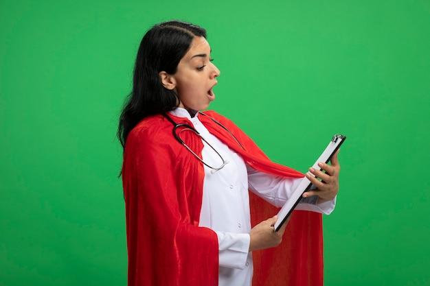 Zaskoczony, młoda dziewczyna superbohatera na sobie szlafrok medyczny ze stetoskopem, trzymając i patrząc na schowek na białym tle na zielono