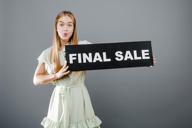Zaskoczony, młoda dziewczyna z ostatecznej sprzedaży znak na białym tle nad szarym
