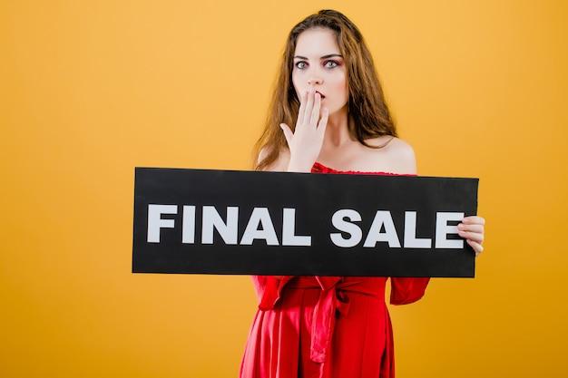 Zaskoczony, młoda kobieta ma ostateczny znak sprzedaży na białym tle nad żółtym
