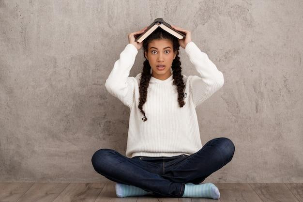 Zaskoczony, młoda kobieta, trzymając książkę nad głową na beżowej ścianie