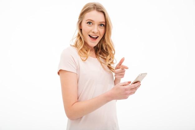 Zaskoczony młoda kobieta za pomocą telefonu komórkowego.