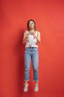 Zaskoczony młoda kobieta zawsze na telefon komórkowy na czerwonej ścianie