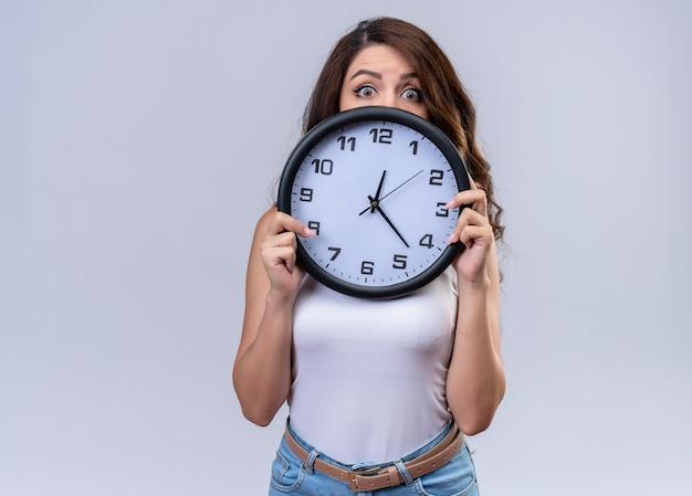 Zaskoczony, młoda piękna dziewczyna trzyma zegar chowając się za nim na odosobnionej białej ścianie z miejsca na kopię