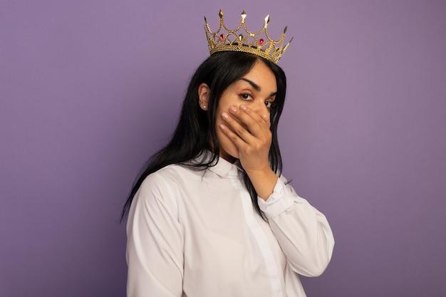 Zaskoczony, młoda piękna dziewczyna ubrana w białą koszulkę i usta zakryte koroną ręką na fioletowym tle