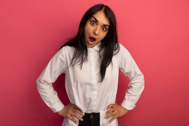 Zaskoczony, młoda piękna dziewczyna ubrana w białą koszulkę kładąc ręce na biodrze na różowym tle
