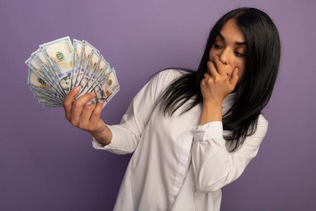 Zaskoczony, młoda piękna dziewczyna ubrana w białą koszulkę, trzymając i patrząc na gotówkę na białym tle na fioletowo