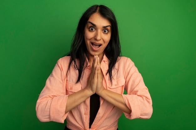 Zaskoczony, młoda piękna dziewczyna ubrana w różową koszulkę przedstawiającą módl się gest na białym tle na zielonej ścianie