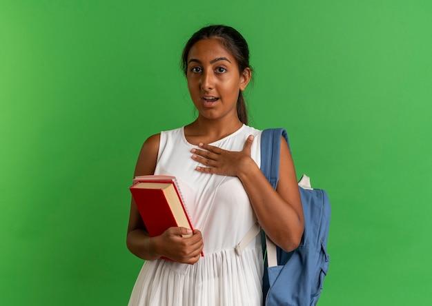 Zaskoczony, młoda uczennica na sobie plecak trzymając książkę z notatnikiem i kładąc rękę na klatce piersiowej na białym tle na zielono