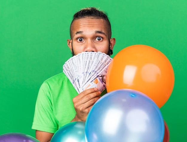 Zaskoczony młody afro-amerykanin ubrany w zieloną koszulkę stojący za balonami pokrytymi twarzą z gotówką odizolowaną na zielonej ścianie