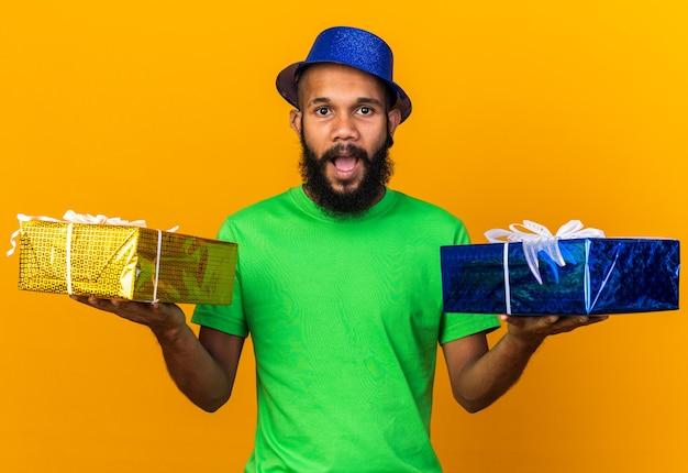 Zaskoczony młody afro-amerykanin w kapeluszu imprezowym, trzymający pudełka na prezenty