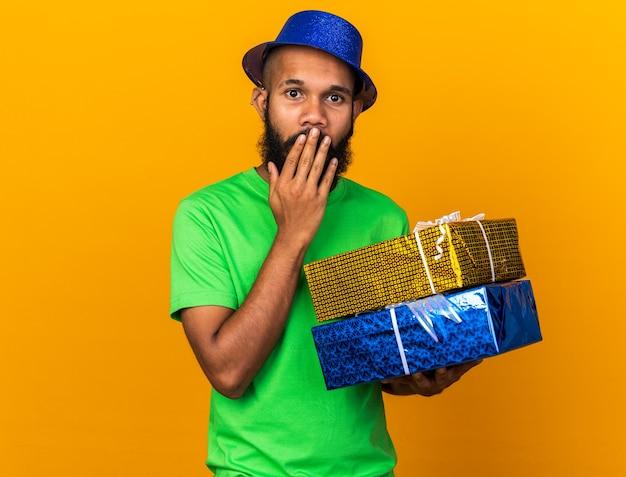 Zaskoczony młody afro-amerykanin w kapeluszu imprezowym, trzymający pudełka z prezentami zakrył usta ręką odizolowaną na pomarańczowej ścianie