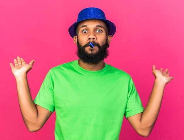 Zaskoczony młody afro-amerykański facet w kapeluszu imprezowym dmuchający gwizdek party rozprzestrzeniający rękę na białym tle na różowej ścianie