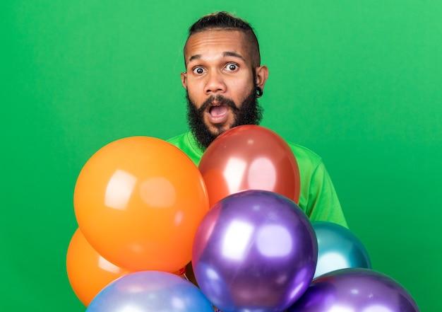 Zaskoczony młody afroamerykanin ubrany w zieloną koszulkę stojący za balonami odizolowanymi na zielonej ścianie