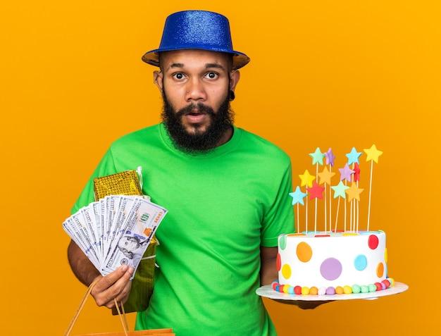 Zaskoczony młody afroamerykanin w imprezowym kapeluszu, trzymający prezenty i ciasto z gotówką