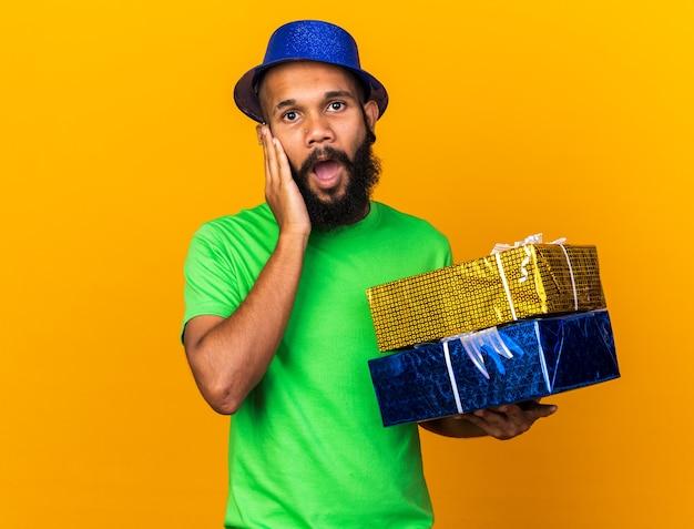 Zaskoczony młody afroamerykanin w imprezowym kapeluszu, trzymający pudełka z prezentami, kładący dłoń na policzku