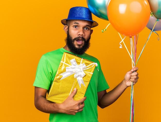 Zaskoczony młody afroamerykanin w kapeluszu imprezowym, trzymający balony z pudełkiem prezentowym na białym tle na pomarańczowej ścianie