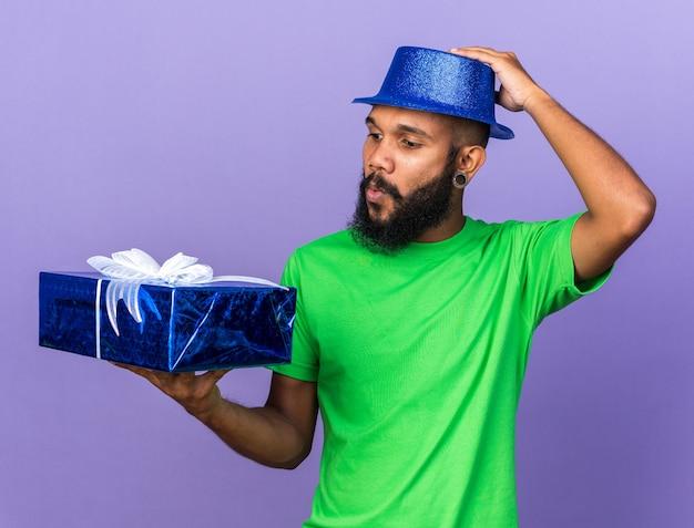 Zaskoczony młody afroamerykanin w kapeluszu imprezowym, trzymający i patrzący na pudełko na białym tle na niebieskiej ścianie