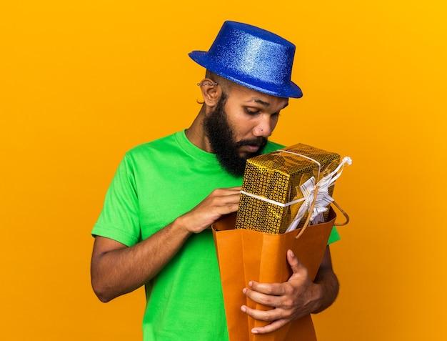 Zaskoczony młody afroamerykanin w kapeluszu imprezowym, trzymający i patrzący na torbę z prezentami