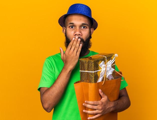 Zaskoczony młody afroamerykanin w kapeluszu imprezowym, trzymający torbę z prezentami zakrytą ustami ręką odizolowaną na pomarańczowej ścianie