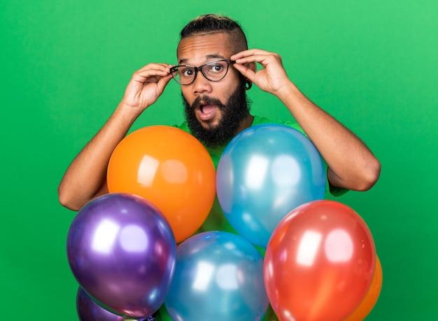 Zaskoczony młody afroamerykański facet ubrany w zieloną koszulkę i okulary stojący za balonami odizolowanymi na zielonej ścianie