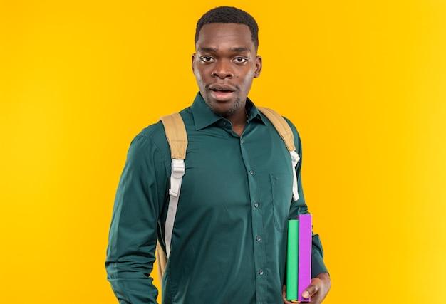 Zaskoczony młody afroamerykański student z plecakiem trzymającym książki i odizolowany na pomarańczowej ścianie z miejscem na kopię
