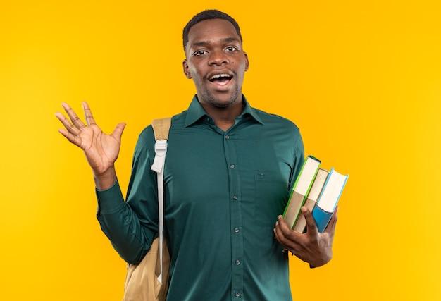 Zaskoczony młody afroamerykański student z plecakiem trzymającym książki i trzymającym rękę otwartą na białym tle na pomarańczowej ścianie z miejscem na kopię