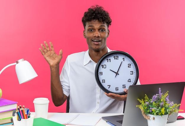 Zaskoczony młody afroamerykański uczeń siedzący przy biurku z szkolnymi narzędziami trzymającymi zegar