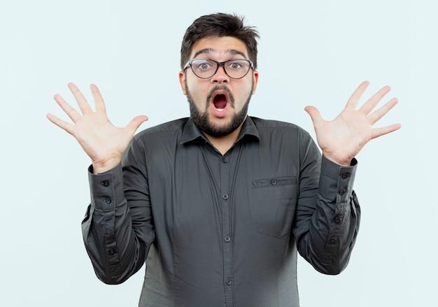Zaskoczony młody biznesmen w okularach rozkłada ręce na białym tle