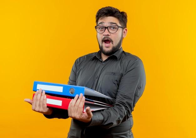 Zaskoczony młody biznesmen w okularach trzymając foldery odizolowane na żółto