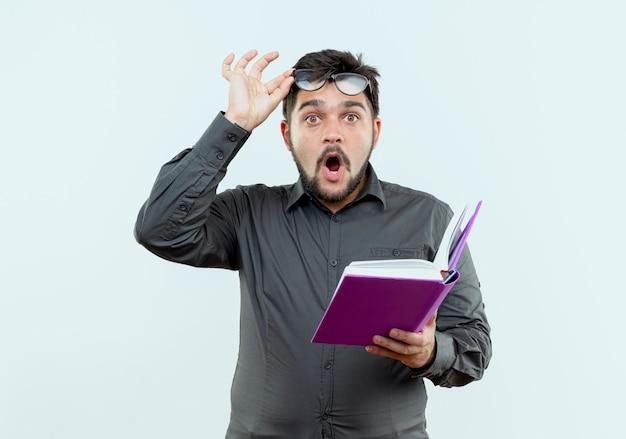 Zaskoczony młody biznesmen w okularach, trzymając książkę i chwycił okulary na białym tle