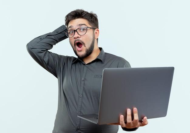 Zaskoczony młody biznesmen w okularach trzymając laptopa i kładąc rękę na głowie na białym tle