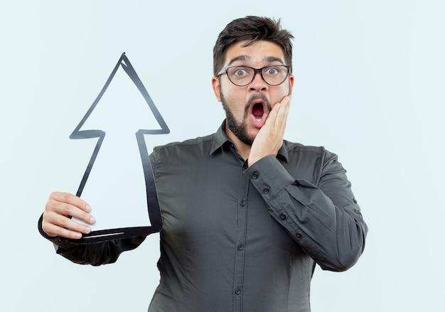 Zaskoczony młody biznesmen w okularach, trzymając znak kierunku i kładąc rękę na policzku na białym tle