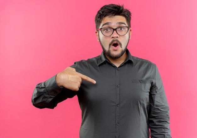 Zaskoczony młody biznesmen w okularach wskazuje na siebie na różowym tle