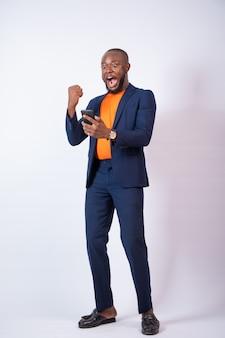 Zaskoczony, młody biznesmen z nigerii świętuje, patrząc na swój telefon