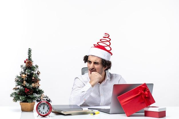 Zaskoczony młody biznesmen z zabawnym czapką świętego mikołaja mówi do kogoś w biurze na białym tle
