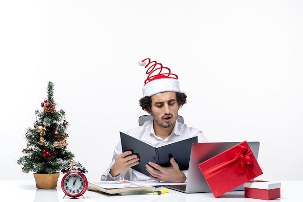 Zaskoczony młody biznesmen z zabawnym czapką świętego mikołaja sprawdzanie informacji w dokumentach w biurze na białym tle