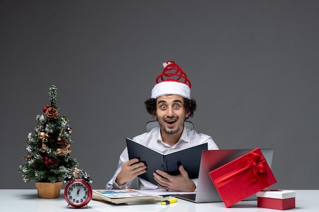 Zaskoczony młody biznesmen z zabawnym czapką świętego mikołaja sprawdzanie informacji w dokumentach w biurze na ciemnym tle