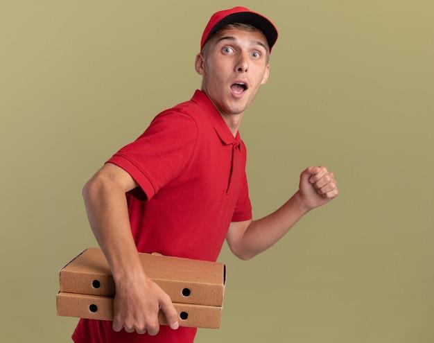 Zaskoczony, młody blond chłopiec na dostawę stoi bokiem, trzymając pudełka po pizzy, udając, że biegnie na oliwkowej zieleni