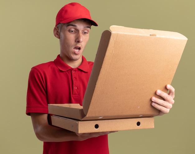 Zaskoczony, młody blond chłopiec na dostawę trzyma i patrzy na pudełka po pizzy na oliwkowej zieleni