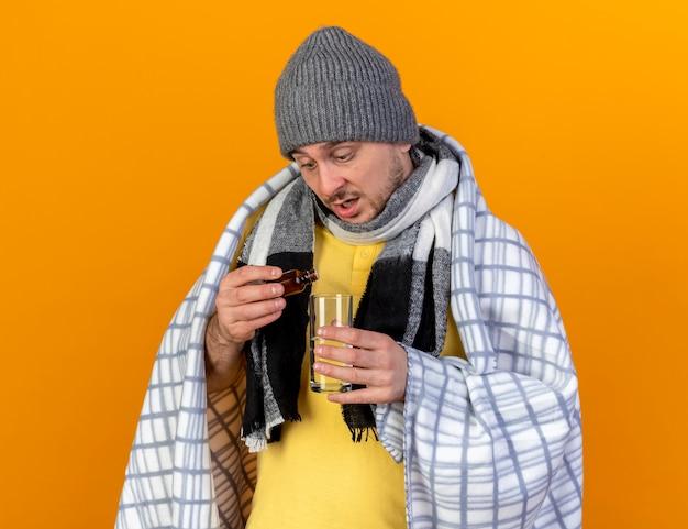 Zaskoczony młody blond chory słowiański mężczyzna w czapce zimowej i szaliku owiniętym w kratę trzyma i patrzy na lekarstwa w szklanej butelce i szklance wody odizolowanej na pomarańczowej ścianie z miejscem na kopię
