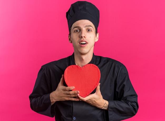 Zaskoczony młody blond kucharz w mundurze szefa kuchni i czapce trzymającej kształt serca, patrząc na kamerę odizolowaną na różowej ścianie