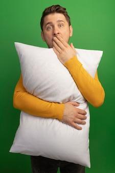 Zaskoczony młody blond przystojny mężczyzna przytula poduszkę, patrząc, jak wkłada rękę do ust na zielonej ścianie