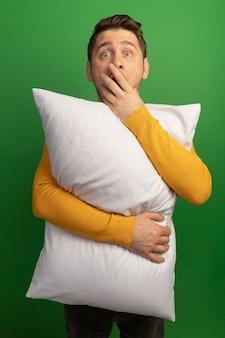 Zaskoczony młody blond przystojny mężczyzna przytula poduszkę patrząc prosto, kładąc rękę na ustach na zielonej ścianie