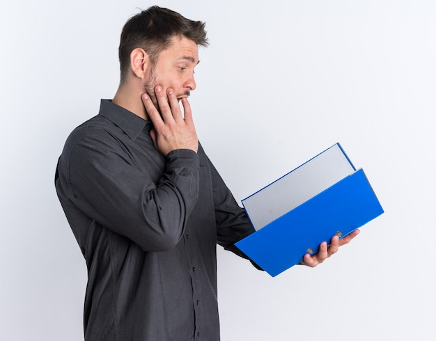 Zaskoczony młody blond przystojny mężczyzna stojący w widoku profilu, trzymający otwarty folder z otwartymi ustami, patrzący na folder izolowany na białej ścianie