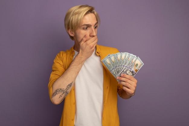 Zaskoczony, młody blondyn na sobie żółtą koszulkę, trzymając i patrząc na gotówkę, kładąc rękę na ustach na fioletowym tle