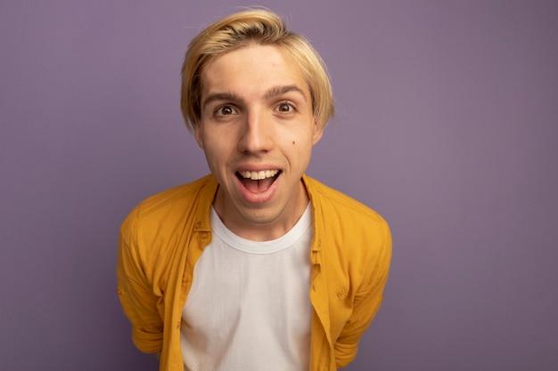 Zaskoczony, młody blondyn na sobie żółtą koszulkę, trzymając się za ręce w pasie