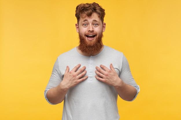 Zaskoczony młody brodaty mężczyzna otwiera usta i uśmiecha się, wskazując na siebie obiema rękami z radosnym wyrazem twarzy.