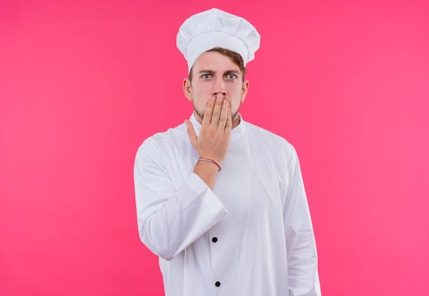Zaskoczony młody brodaty szef kuchni w białym mundurze, trzymając rękę na ustach, patrząc na różową ścianę
