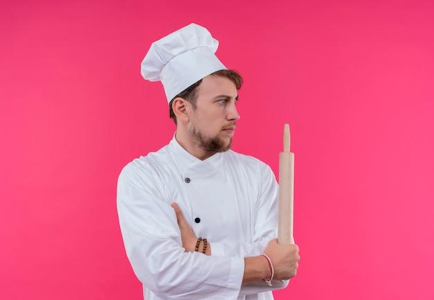 Zaskoczony młody brodaty szef kuchni w białym mundurze, trzymając wałek do ciasta, patrząc z boku na różową ścianę