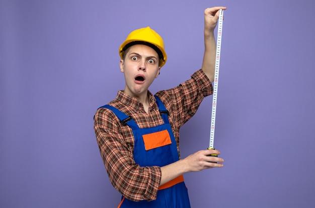 Zaskoczony młody budowniczy mężczyzna ubrany w mundur rozciągający taśmę mierniczą